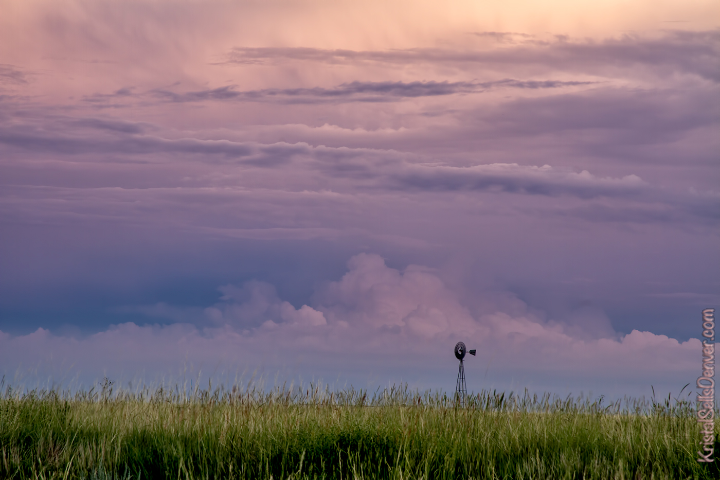 A solitary windmill sits on the horizon at sunset